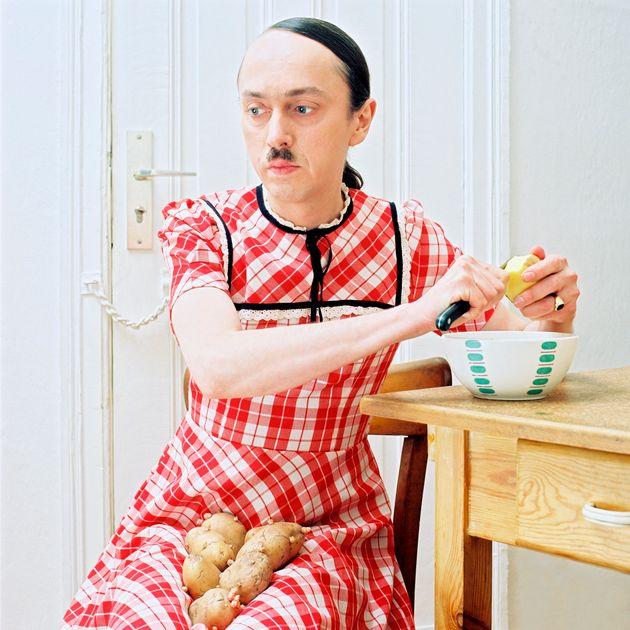 아돌프 히틀러의 얼굴을 한 남성이 여성의 옷을 입고 감자를 깎고