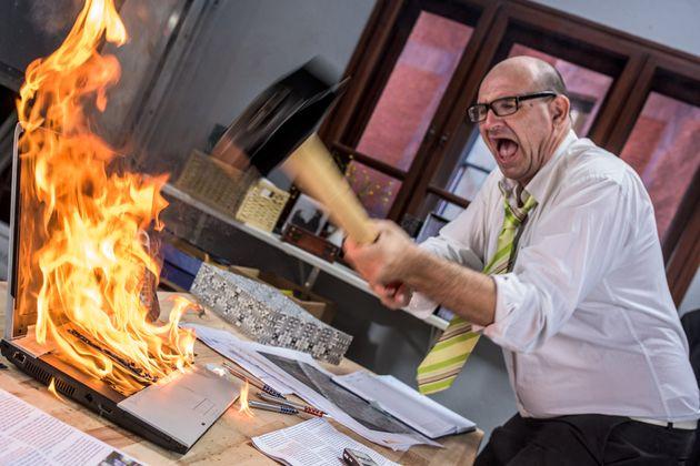 불에 타고 있는 노트북을 남자가 망치로 부수고
