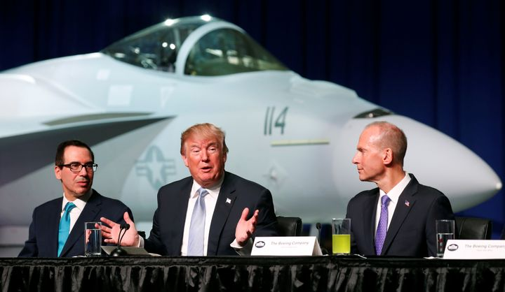 President Donald Trump sits between Treasury Secretary Steve Mnuchin (L) and Boeing Chairman and CEO Dennis Muilenburg (R) du