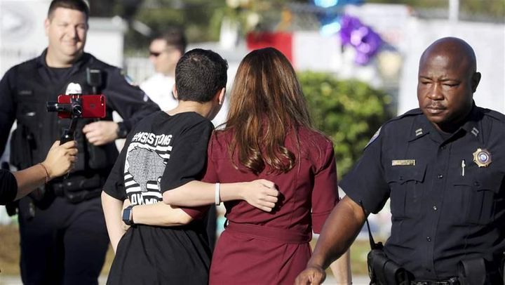 Camille Aponte walks with her son, Nelson Laboy, as he heads into school at Marjory Stoneman Douglas High School for the firs