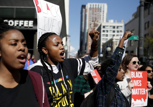 People carry signs and march at a Black Lives Matter protest in Seattle, Washington, in April