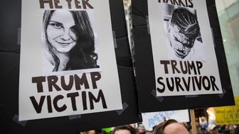 NEW YORK, NY - AUGUST 14: Protesters carry posters of Heather Heyer and Deandre Harris during an anti-President Donald Trump demonstration outside of Trump Tower August 14, 2017 in New York City. Heyer was killed by an automobile driven by James Alex Fields over the weekend by in Charlottesville, Virginia and Harris was seriously beaten by right-wing extremists, also in Charlottesville, Virginia. Security throughout the area is high as President Donald Trump is expected to arrive at his residency in the tower later tonight, his first visit back to his apartment since the inauguration. (Photo by Robert Nickelsberg/Getty Images)