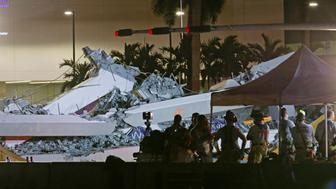 First responders are shown as rescue efforts continue after a pedestrian bridge collapsed at Florida International University in Miami, Florida, U.S., March 15, 2018.  REUTERS/Joe Skipper