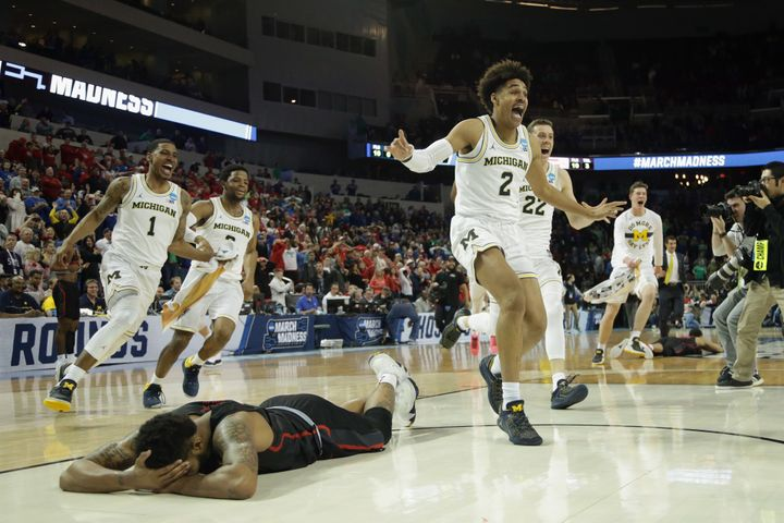 Jordan Poole and teammates celebrate Poole's 3-point buzzer beater for a 64-63 win as Devin Davis of the Houston Cougars is s