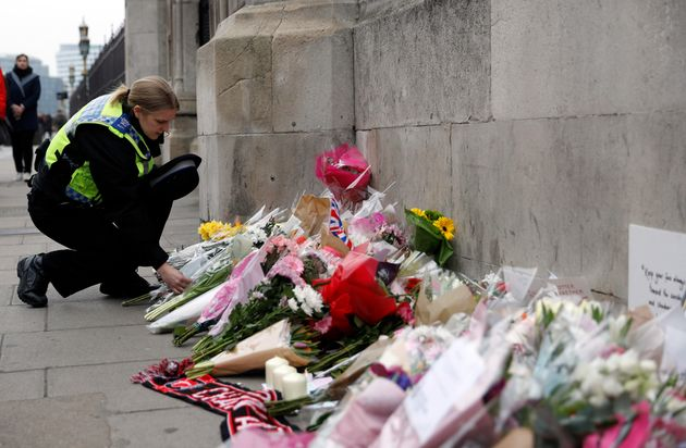 A police officer lays a floral tribute near Westminster Bridge following the