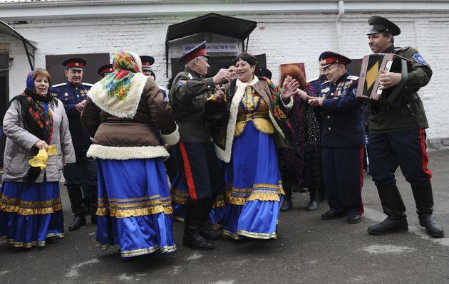 코사크 커뮤니티의 사람들은 투표소 밖에서 춤을