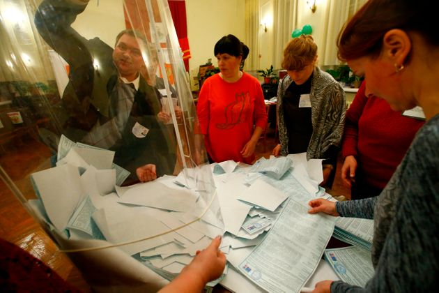 Members of a local election commission empty a ballot box before starting to count votes during the presidential...