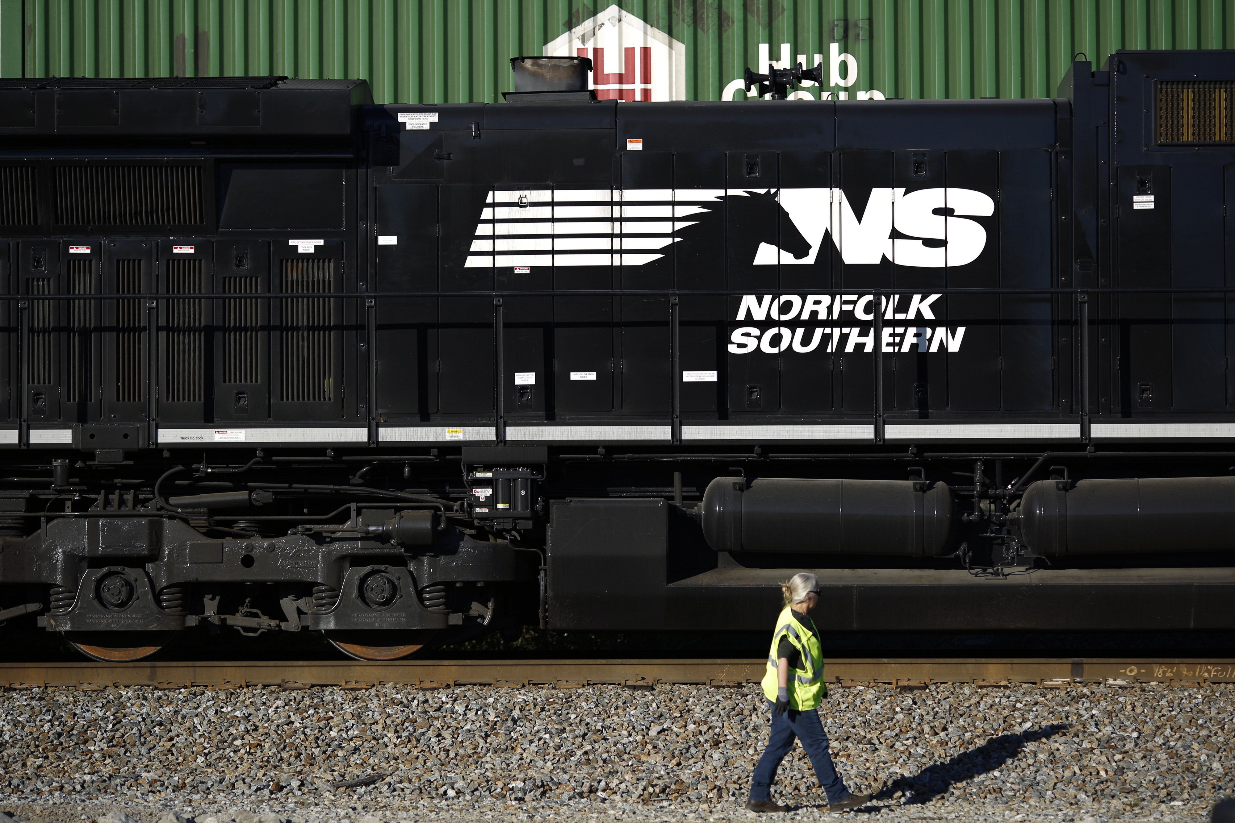 A conductor walks past a Norfolk Southern Railway Corp. freight locomotive in Burnside, Kentucky. Two of the compan