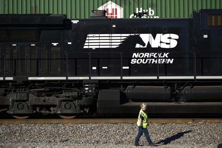 A conductor walks past a Norfolk Southern Railway Corp.freight locomotive in Burnside, Kentucky.Two of the compan