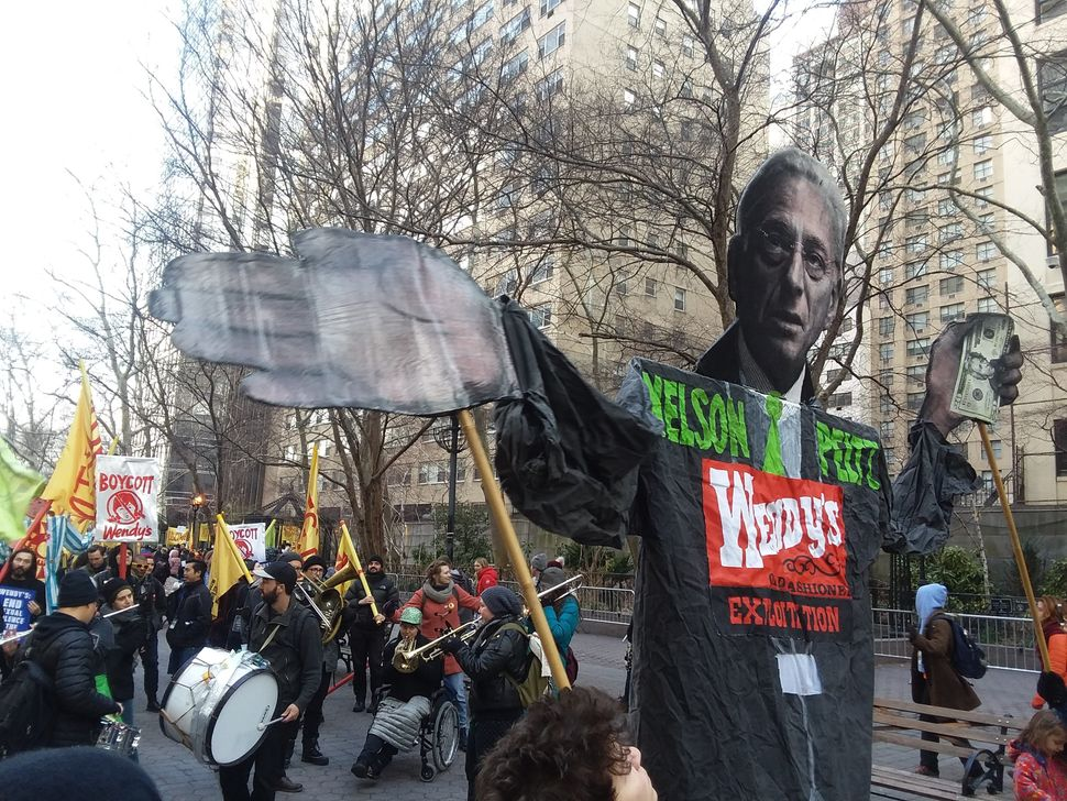 Protesters carry a puppet of Wendy's board chairman and hedge fund investor Nelson Peltz.
