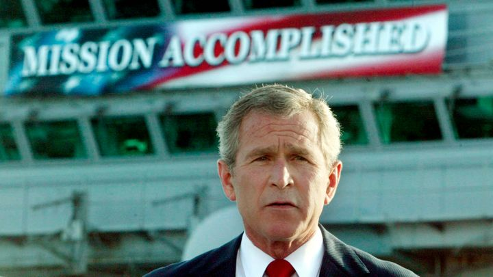 "George W. Bush stands in front of the infamous ""Mission Accomplished"" banner on the USS Abraham Lincoln to declare the end of"