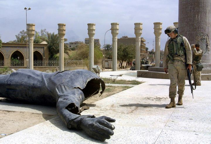 U.S. Marines walk pass a dismantled statue of Saddam Hussein on Baghdad's al-Fardous square on April 10, 2003.