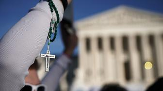 WASHINGTON, DC - JANUARY 19:  A pro-life activist holds up a rosary as he passes in front the U.S. Supreme Court during the 2018 March for Life January 19, 2018 in Washington, DC. Activists gathered in the nation's capital for the annual event to protest the anniversary of the Supreme Court Roe v. Wade ruling that legalized abortion in 1973.  (Photo by Alex Wong/Getty Images)