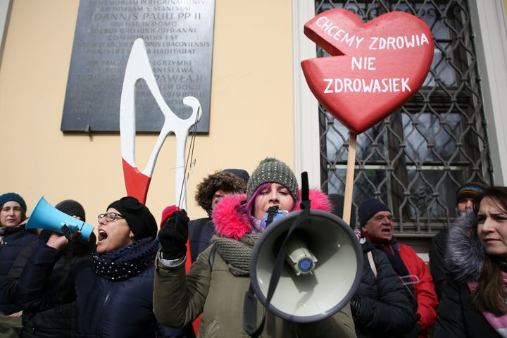 Women protest a stricter anti-abortion measure in front of archdiocese headquarters in Krakow, Poland, on March 18, 2018.