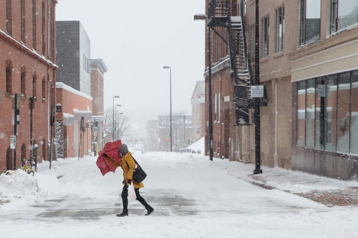 A woman in Portland, Maine, uses an umbrella to block the blowing snow while walking near Monument Square during last we