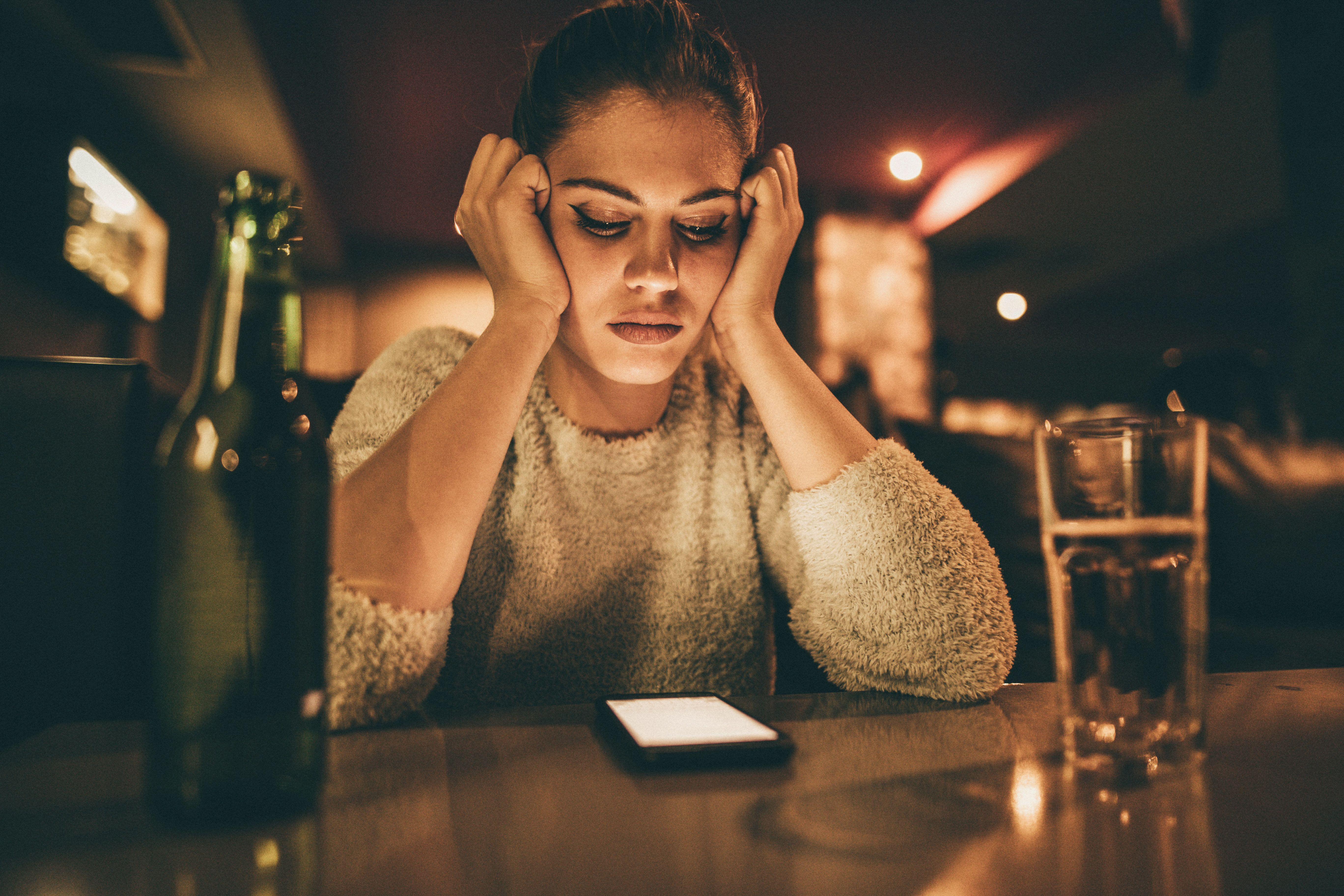 Depressed woman sitting in a bar and looking at her cell phone while waiting for a call from her boyfriend.
