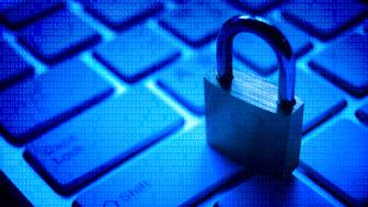 A security lock on computer keyboard with blue digital background