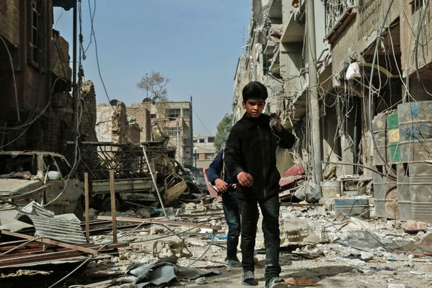 Children walk among the rubble after an airstrike in Douma, in the eastern Ghouta region of Syria, on...