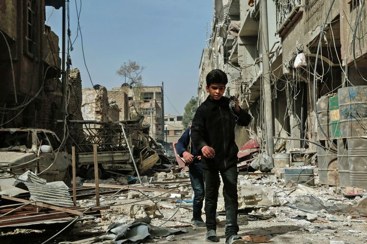 Children walk among the rubble after an airstrike in Douma, in the eastern Ghouta region of Syria, on Monday. The latest stri