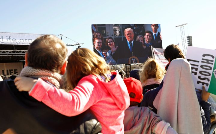 Participants watch as President Donald Trump speaks by satellite from the nearby White House to attendees of the March for Li