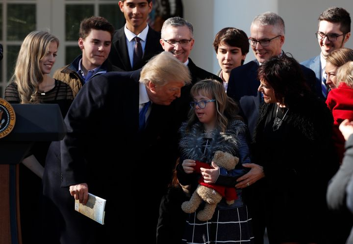 Trump greets a young girl among families gathered in the White House Rose Garden as he addresses the annual March for Life ra