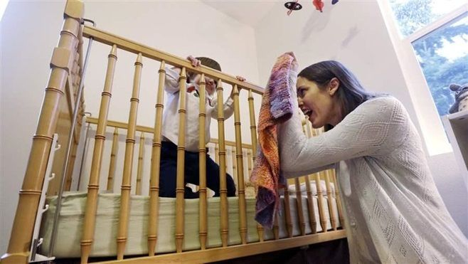 Seattle resident Marita Graube plays peek-a-boo with her daughter, Ayame, as the girl sits in her crib and atop an organic ma