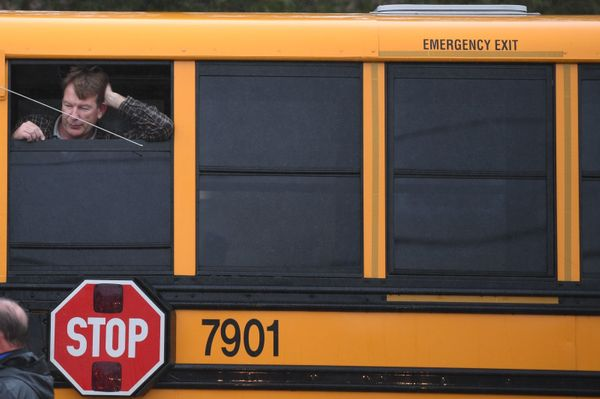 A man looks out of a school bus.