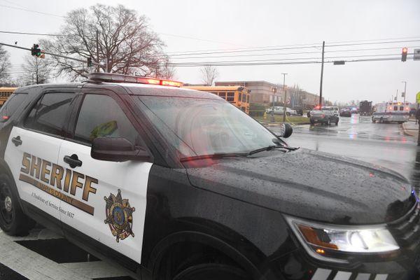 A sheriff's car is seen near the school.
