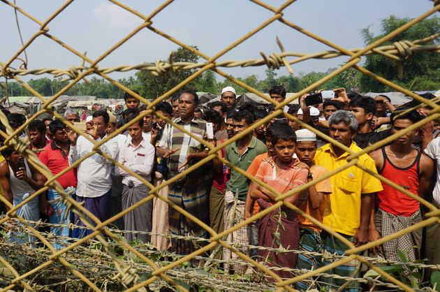 Rohingya Muslims gather behind Myanmar's border lined with barbed wire fences in Maungdaw district, located...