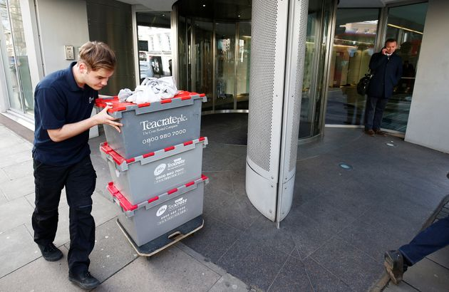 A man wheels storage crates from the building that houses the offices of Cambridge Analytica in central...