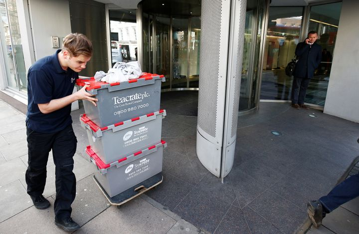 A man wheels storage crates from the building that houses the offices of Cambridge Analytica in central London, Britain, on T