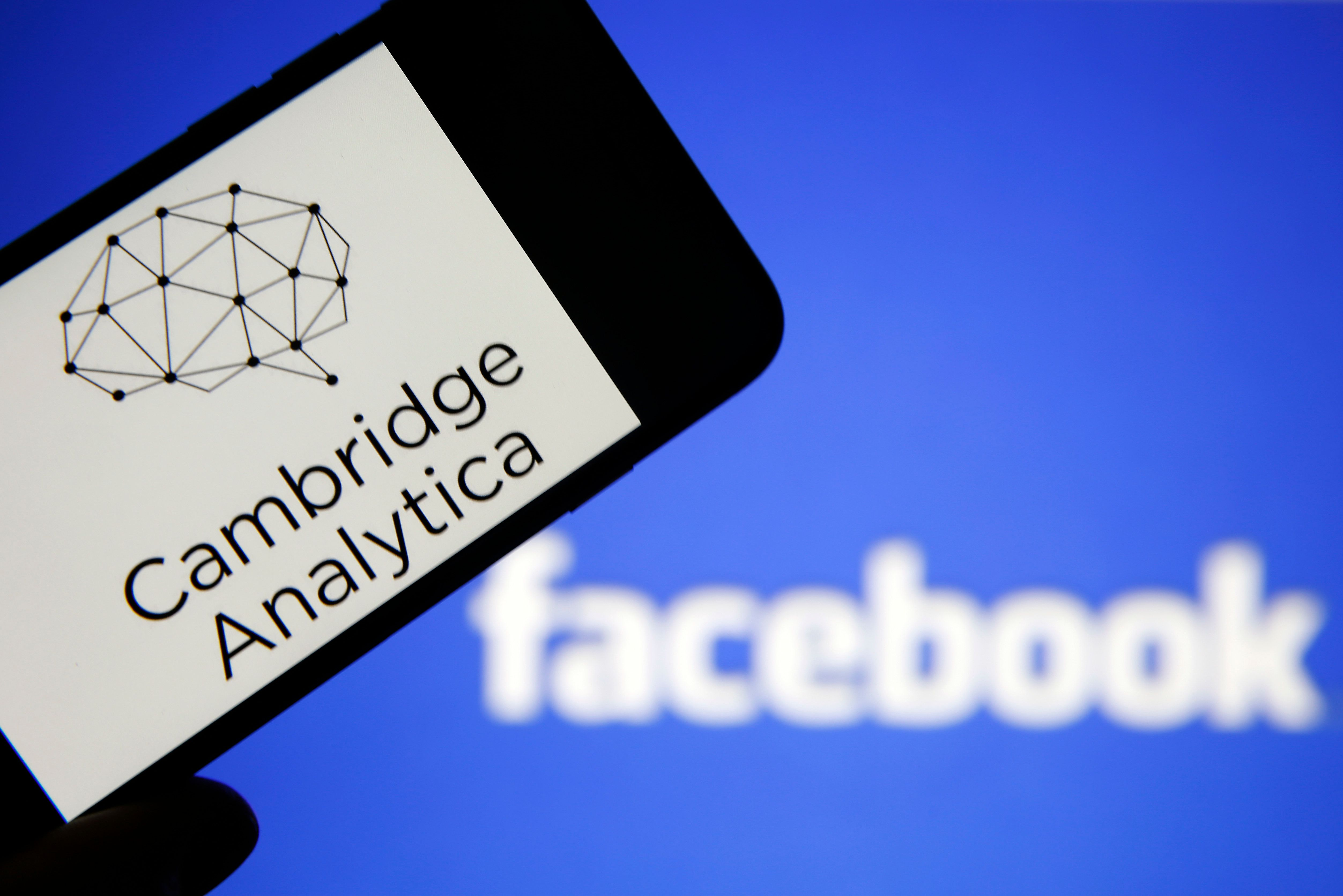 PARIS, FRANCE - MARCH 20:  In this photo illustration the logo of the strategic communication company 'Cambridge Analytica' is seen on the screen of an iPhone in front of a computer screen showing a Facebook logo on March 20, 2018 in Paris, France. Cambridge Analytica is accused of collecting the personal information of 50 million users of the Facebook social network without their consent and would have used it to develop software to predict and influence voter voting during the campaign American election according to the New York Times and the Guardian. Facebook share price fell by more than 5% Monday shortly after the opening of Wall Street.  (Photo Illustration by Chesnot/Getty Images)