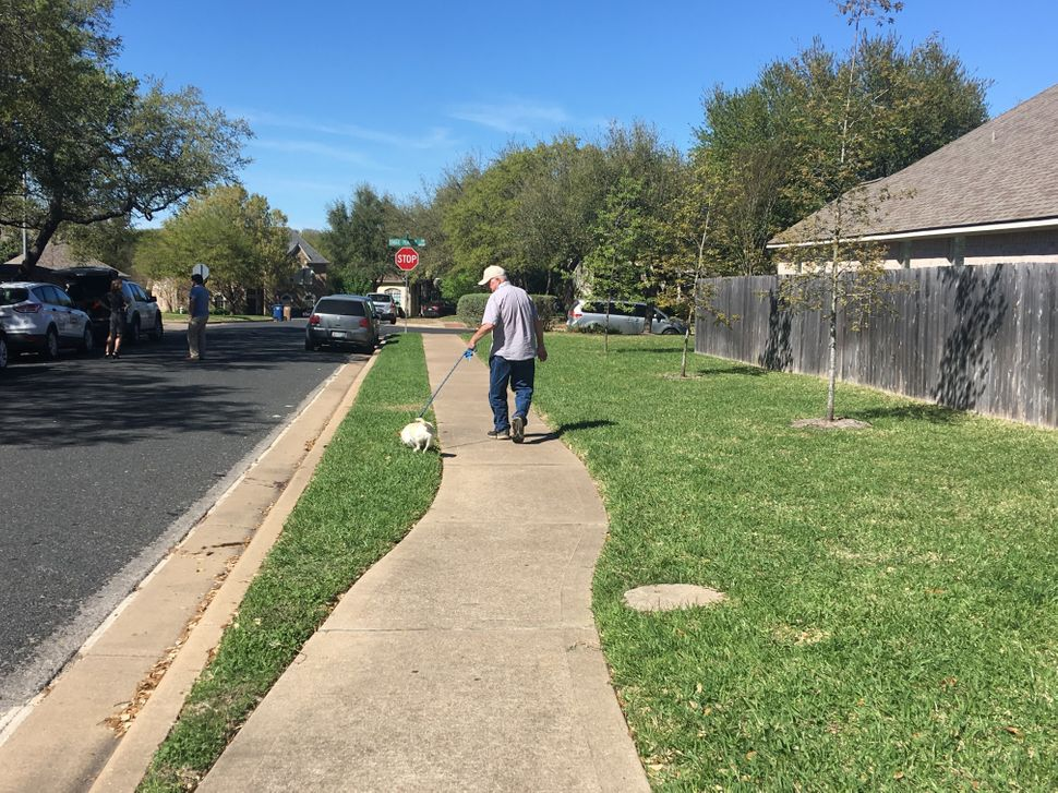 James Barnes walks his dog toward the spot where, days earlier, a tripwire bomb detonated in his sleepy neighborhood in Austi