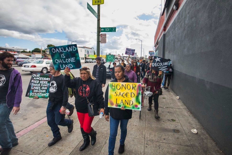 Advocates march with signs on the day of the land-honoring ceremony for the plot in Oakland.