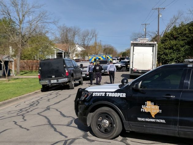 Law enforcement officers are seen blocking a street leading to the home of Mark