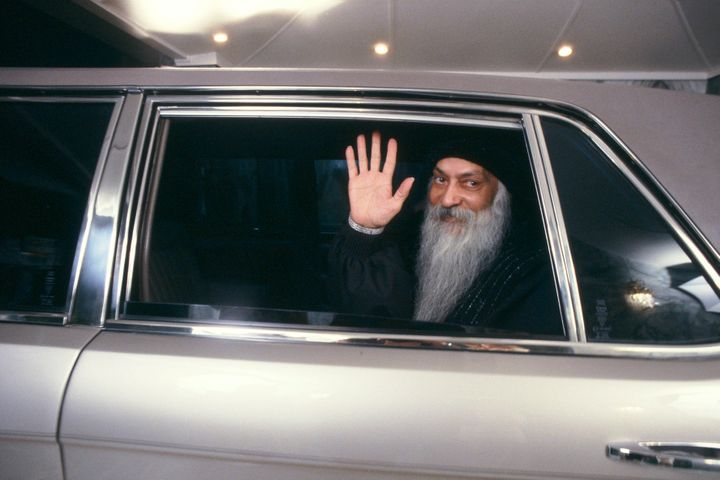 Rajneesh waving from a car.