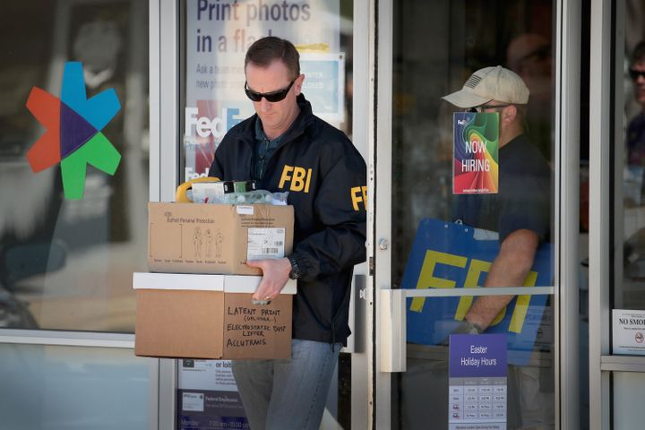 FBI agents collect evidence at a FedEx facility following an explosion at a nearby sorting center on Tuesday in Sun