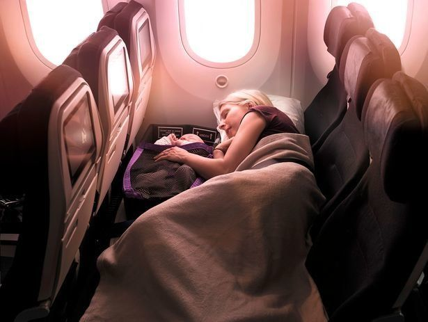 A parent lying down with a baby in an infant pod on an Air New Zealand flight.