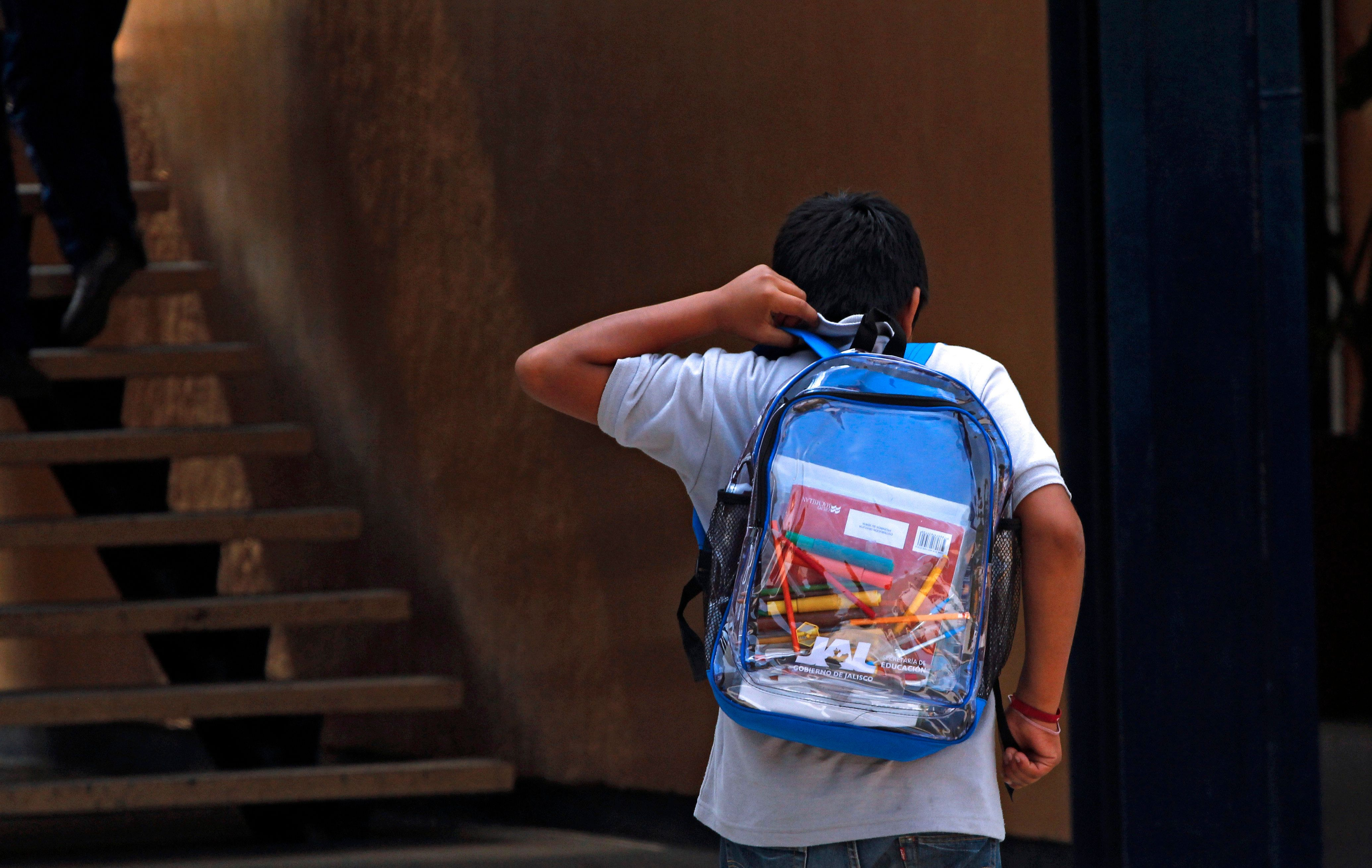 A secondary school student walks carrying his new transparent backpack  in Guadalajara, Mexico on October 25, 2012. The transparent backpacks are part of the program 'Escuela Segura' (Safe School ) to avoid violence in schools and in the coming days the State Government will deliver 10,000 more of these hoping the measure will help teachers and parents see what students are taking to school. AFP PHOTO/Hector Guerrero        (Photo credit should read HECTOR GUERRERO/AFP/Getty Images)
