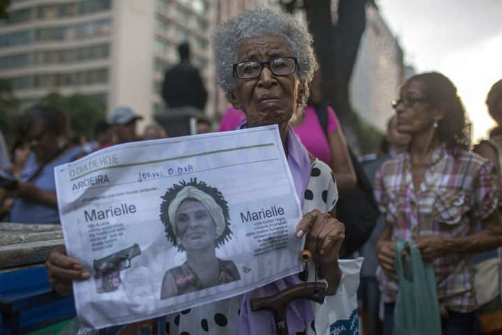 A protester in Rio de Janeiro carries a newspaper featuring Brazilian councilwoman and activist Marielle Franco on March 20,