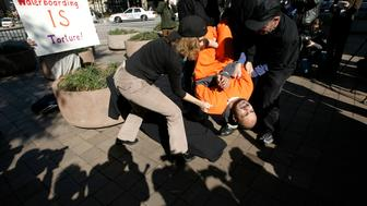 Demonstrator Maboud Ebrahimzadeh is lowered onto the board during a simulation of waterboarding outside the Justice Departement in Washington November 5, 2007. The confirmation of Bush nominee Michael Mukasey as U.S. Attorney General is in jeopardy after Mukasey's refusal to state whether the interrogation techinque known as waterboarding violates U.S. laws banning torture.    REUTERS/Kevin Lamarque  (UNITED STATES)