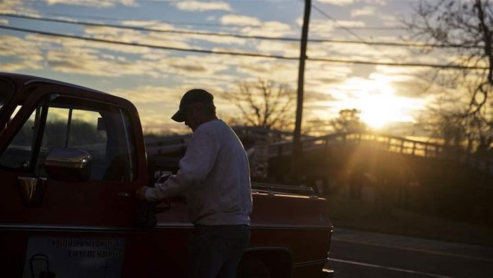 A customer gets into his car after shopping at a convenience store as the sun rises in Lula, Georgia. Rural areas gained popu