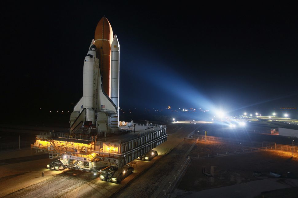 Space shuttle Discovery rolls to the launch pad after emerging from NASA's vehicle assembly building atop a crawler transport