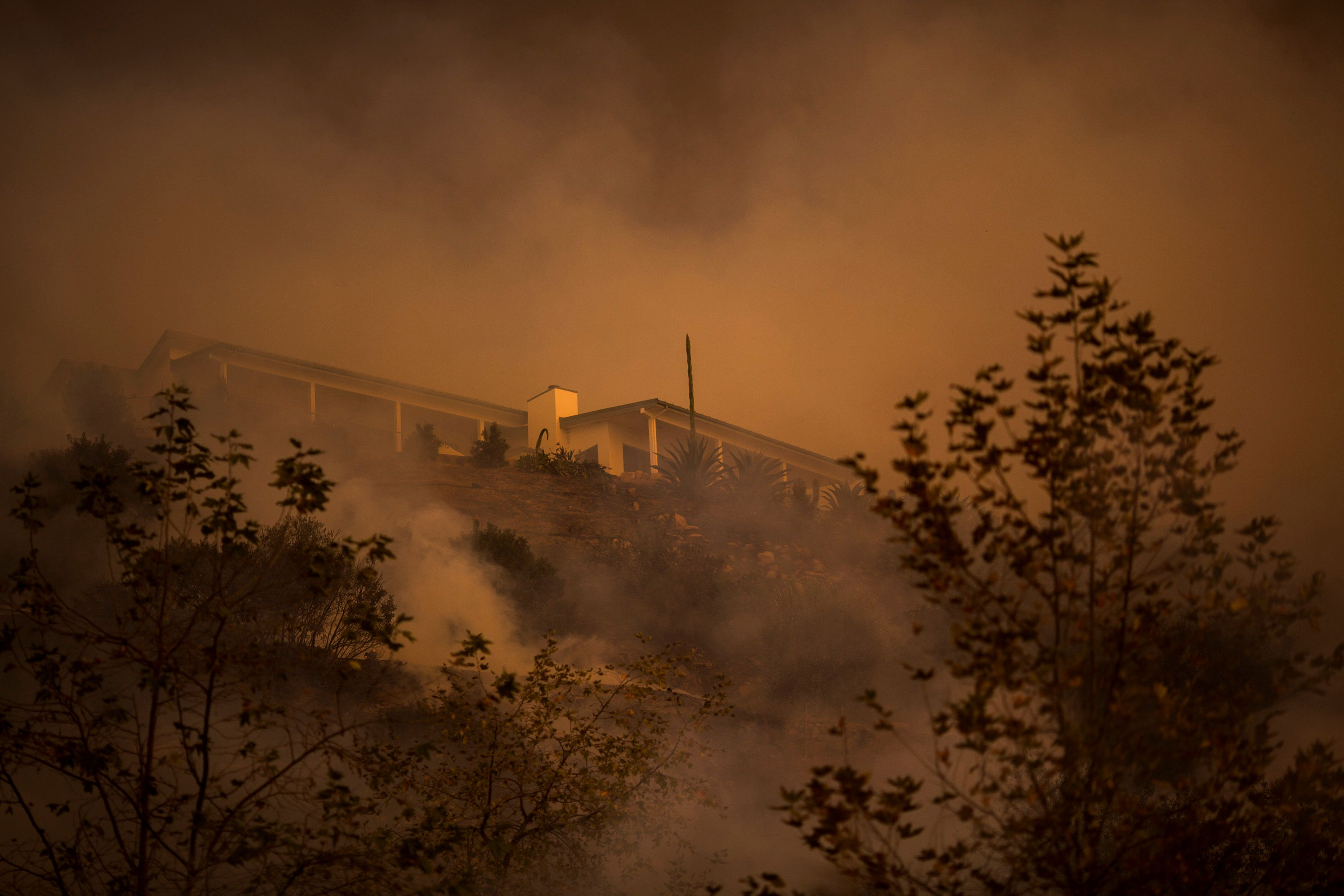 MONTECITO, CA - DECEMBER 16: Fire passes between homes at the Thomas Fire on December 16, 2017 in Montecito, California. The National Weather Service has issued red flag warnings of dangerous fire weather in Southern California for the duration of the weekend. Prior to the weekend, Los Angeles and Ventura counties had 12 consecutive days of red flag fire warnings, the longest sustained period of fire weather warnings on record. The Thomas Fire is currently the fourth largest California fire since records began in 1932, growing to 400 square miles and destroying more than 1,000 structures since it began on December 4. (Photo by David McNew/Getty Images)
