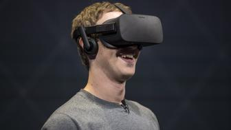 Mark Zuckerberg, chief executive officer and founder of Facebook Inc., demonstrates an Oculus Rift virtual reality (VR) headset and Oculus Touch controllers as the gives a demonstration during the Oculus Connect 3 event in San Jose, California, U.S., on Thursday, Oct. 6, 2016. Facebook Inc. is working on a new virtual reality product that is more advanced than its Samsung Gear VR, but doesn't require connection to a personal computer, like the Oculus Rift does. Photographer: David Paul Morris/Bloomberg via Getty Images