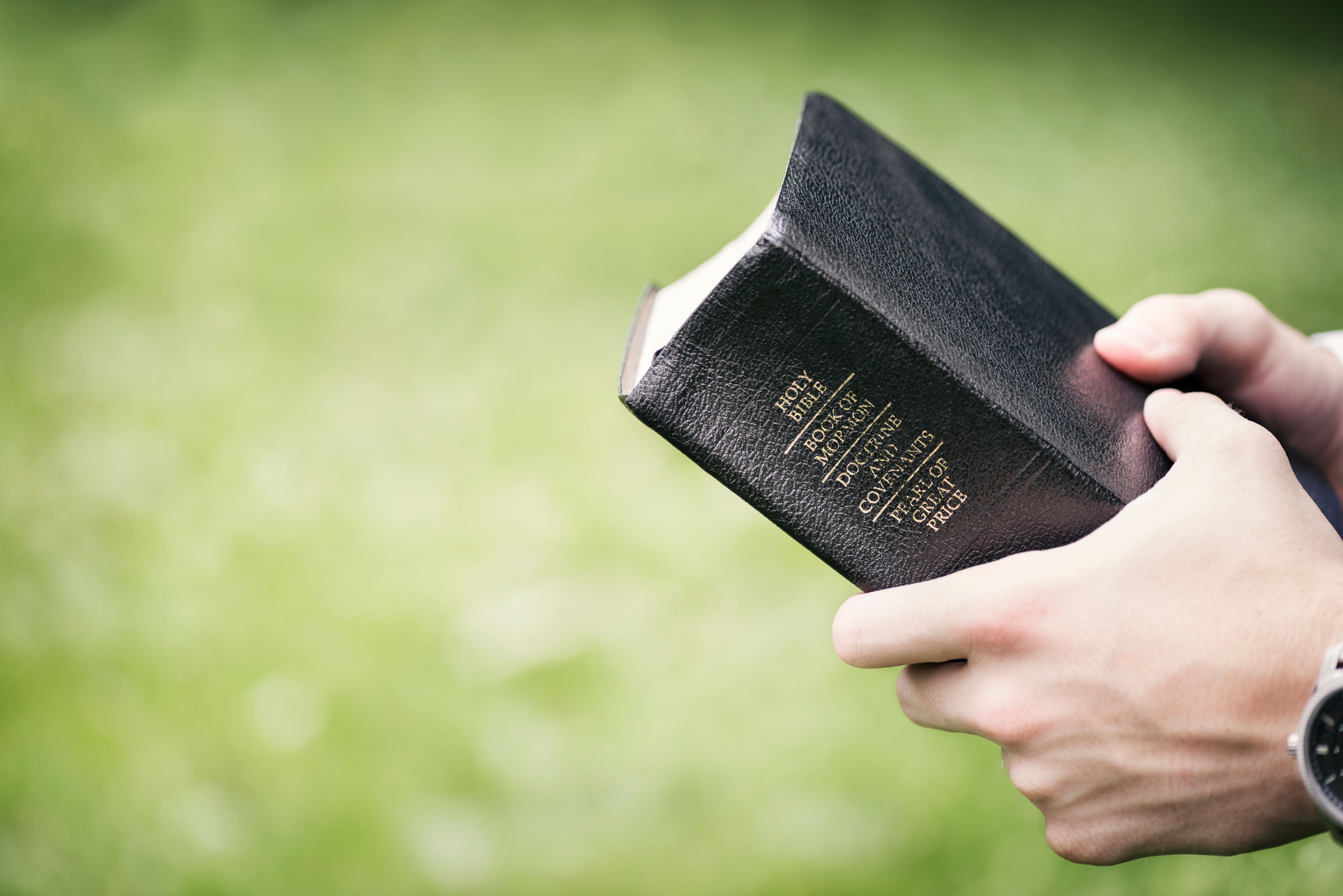 Hands of a young male missionary holding the 'Quad' containing The Holy Bible, The Book of Mormon, Doctrine and Covenants and The Pearl of Great Price.