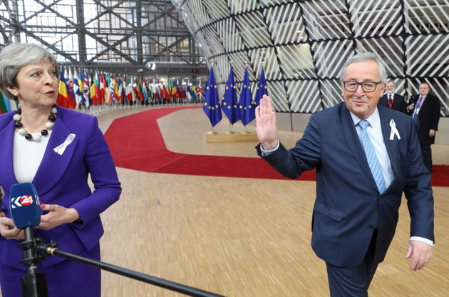 Theresa May speaks to the press as European Commission president Jean-Claude Juncker greets her as they...
