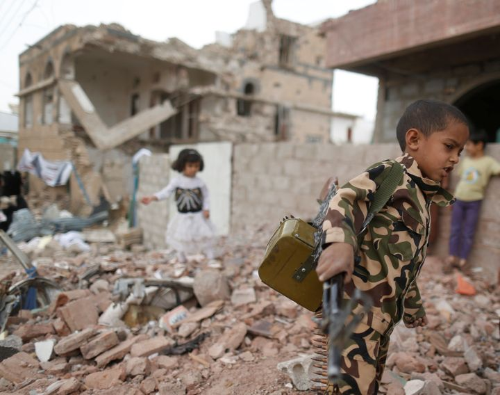A boy carries a toy gun next to destroyed houses on June 21, 2016, during a vigil marking a year since a Saudi-led airstrike on a residential area in Sanaa, Yemen.
