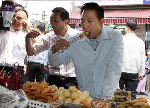 2009년 6월25일 이명박 전 대통령이 서울 동대문구 이문동 골목상가를 찾아 어묵을 먹고