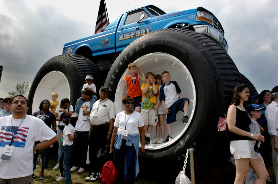"Children stand in the wheel wells of Bigfoot 5, Ford's monster truck, on June 13, 2003. The monster truck was the <a href=""ht"